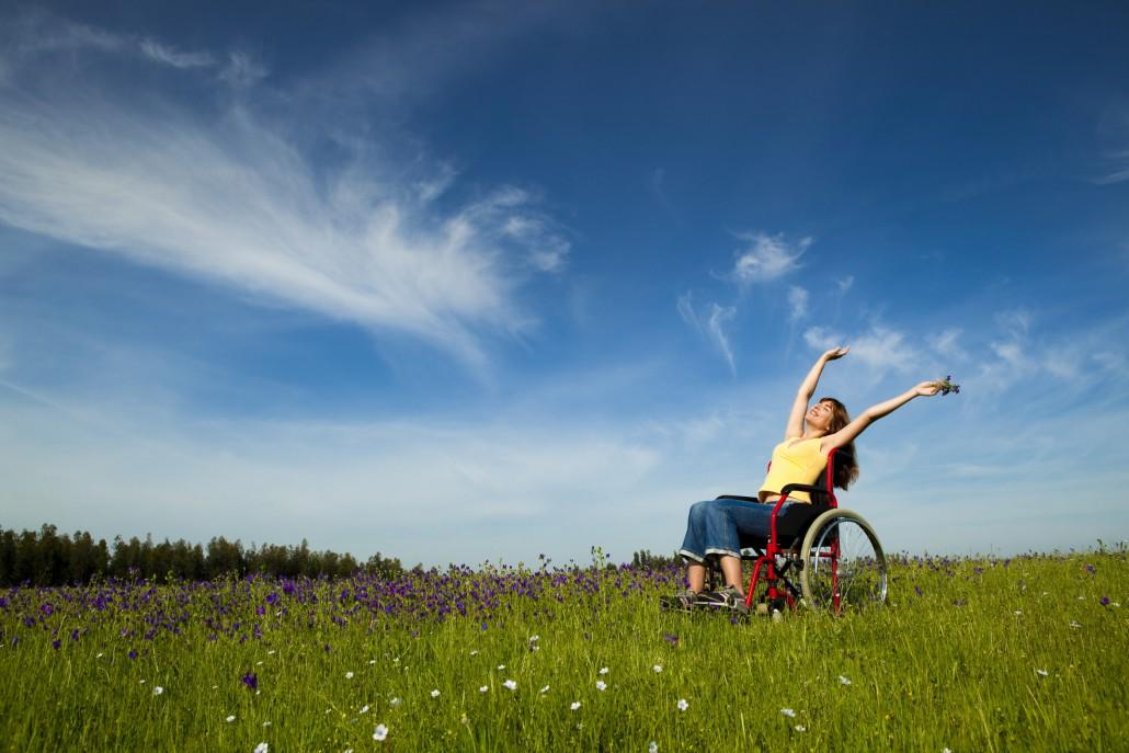 Eine Frau im Rollstuhl auf einer Blumenwiese