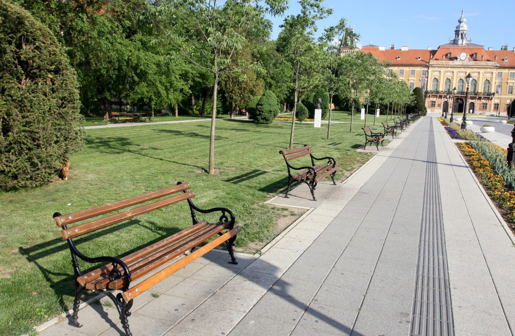 Bänke in einem Park und ein Gehweg mit Blindenleitsystem. Barrierefreiheit