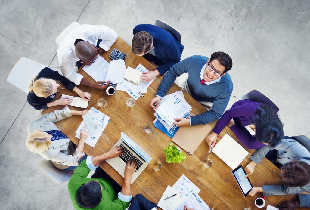 Verschiedene Mitarbeiter und Mitarbeiterinnen arbeiten bei einer Konferenz